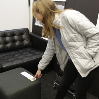 A woman presses a button on an IKEA price tag