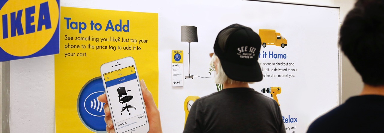 A woman scans an IKEA smart tag with her phone.